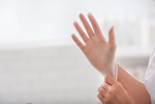 ゴム手袋をつける人の手