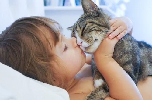 猫とキスをする子供