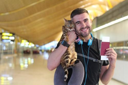 パスポートと猫を持った男性