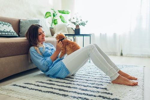 ソファーの前に座る女性の膝の上にいる茶トラ猫