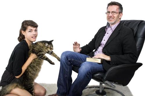 猫を抱っこして近づく女性を嫌そうな顔で拒否する男性