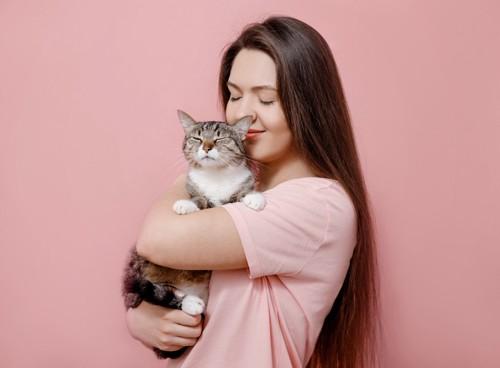 目を閉じて抱っこする女性と目を閉じる細める猫