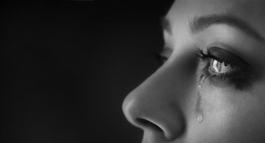 目から涙が出ている女性の顔アップ