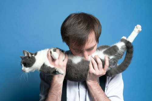 猫を持ち上げてお腹に顔を埋める男性