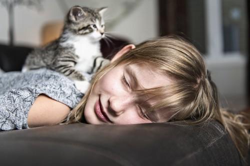 うつ伏せで眠る女性の背中に乗る子猫