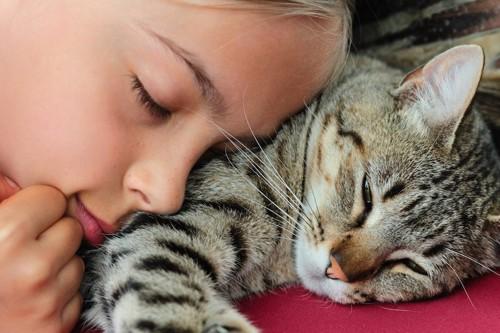 寝ている猫に顔を近づける女性