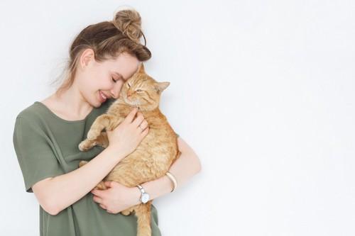 茶トラ猫を抱っこして顔を寄せる女性