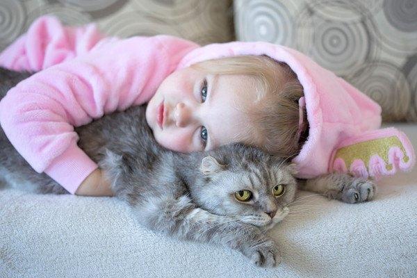 子供に抱きつかれる猫