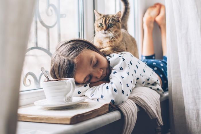 うつ伏せで眠る女の子の背中に乗る子猫