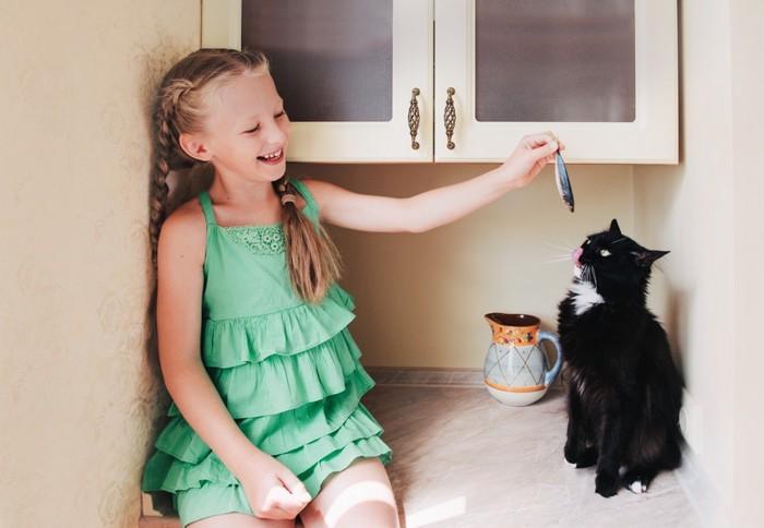 猫に魚をあげる女の子