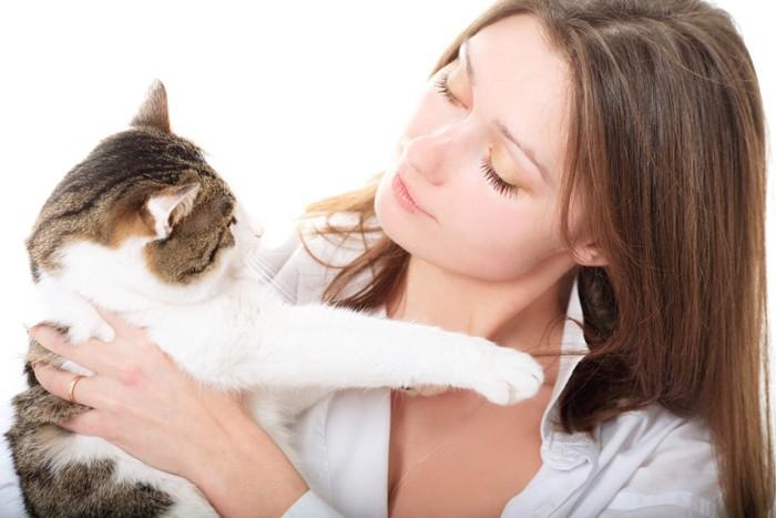 女性の髪の毛に手を伸ばす猫