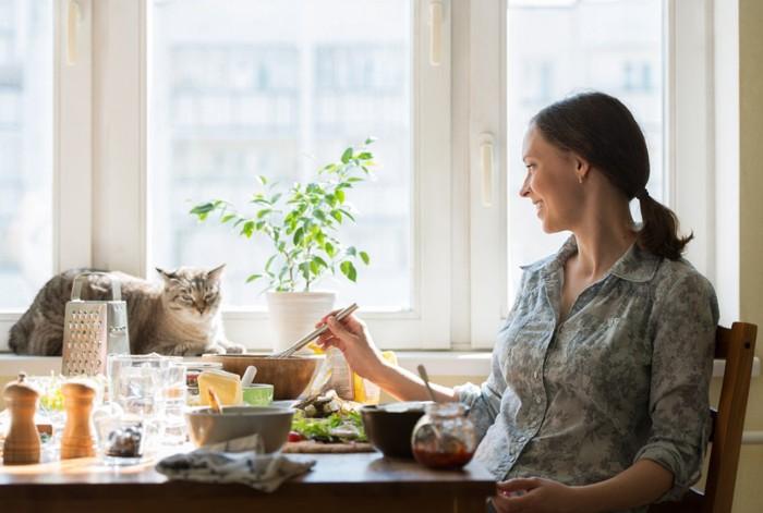 食卓にいる女性と猫