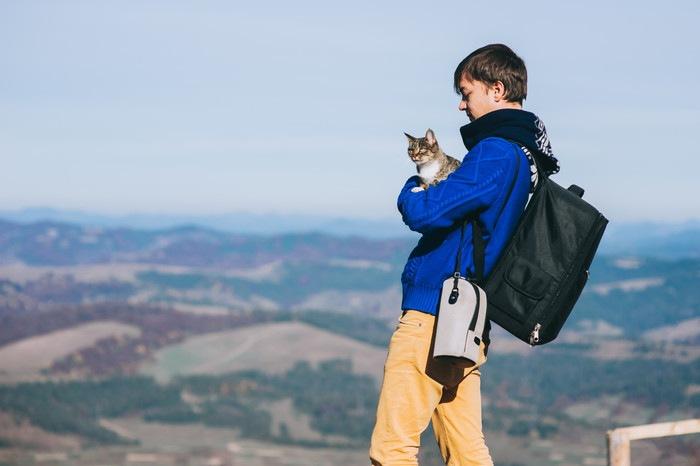 山にいる男性と抱かれている猫