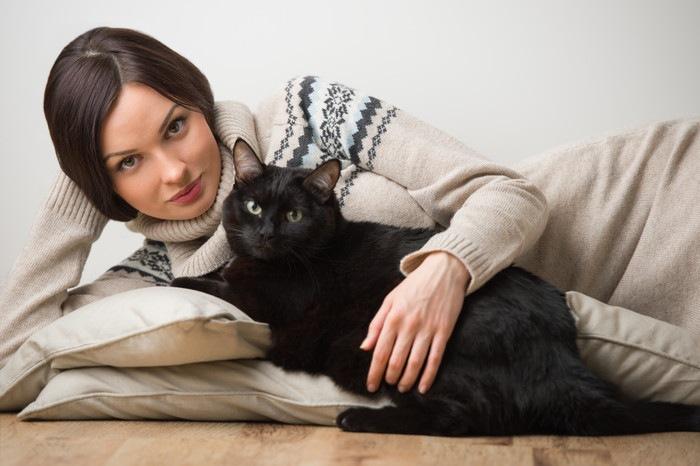 ベッドの上の猫と女性