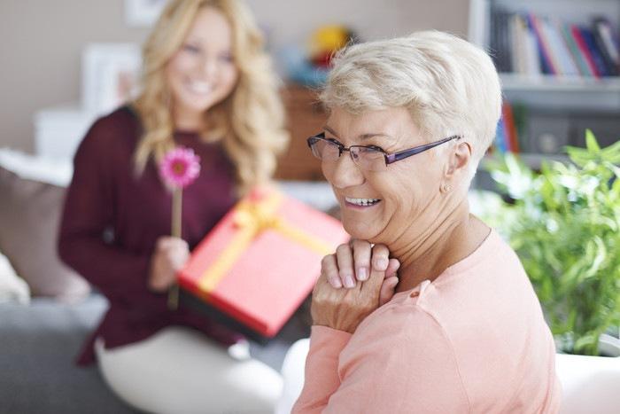 奥にガーベラとプレゼントを持った娘。手前のめがねをかけたおばあちゃんが満面の笑みで喜んでいる画像