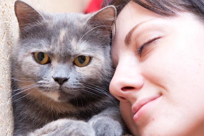 目を閉じて猫の顔に顔を近づける女性