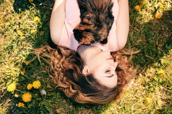 猫を抱っこして寝転がる女性
