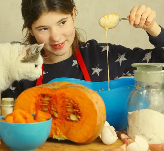 料理をする女の子と猫