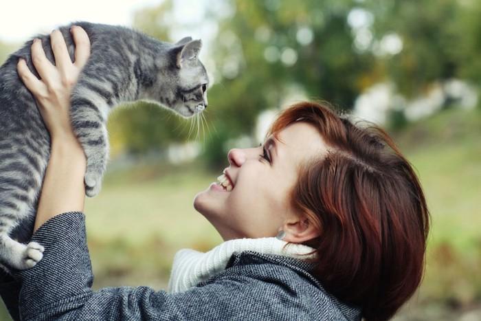 猫を抱き上げる笑顔の女性