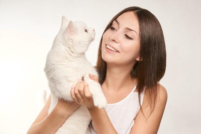笑顔の女性に抱っこされている白猫