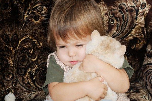 猫を子供が抱き締める