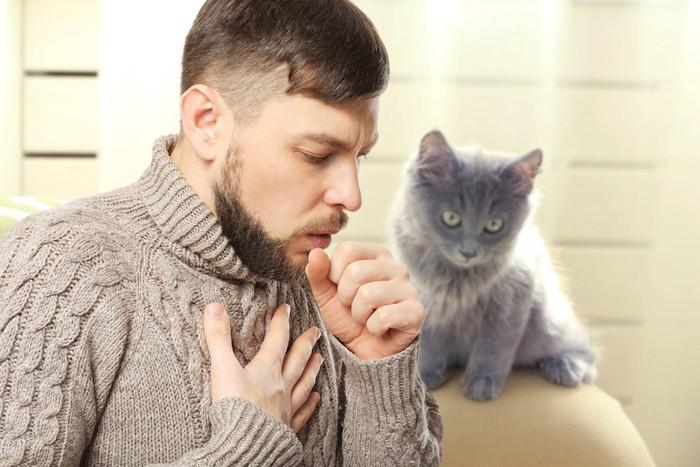 咳をしている男性とグレーの猫