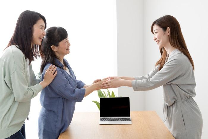 手を取り合う女性の写真