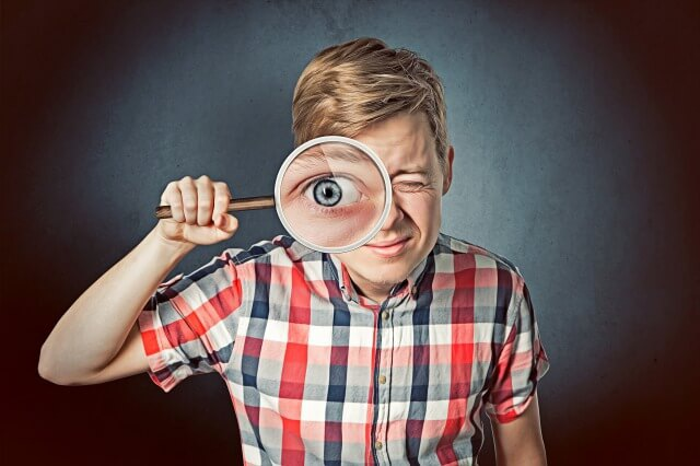 虫眼鏡を覗き込んでいる人