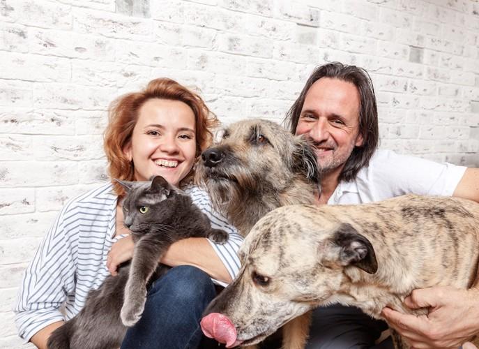 犬と猫を抱きしめる笑顔のカップル