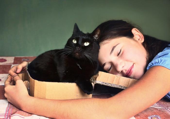 段ボールの中の黒猫に顔を近づける女性