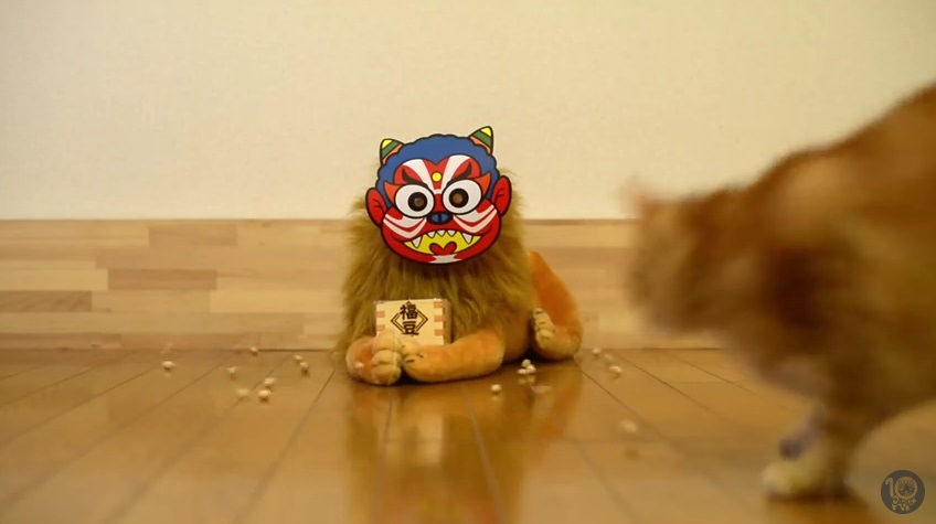 鬼の面を付けたぬいぐるみと駆け寄る猫