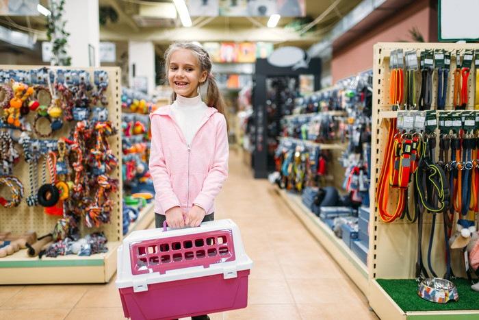 ペットショップでキャリーバッグを持つ少女