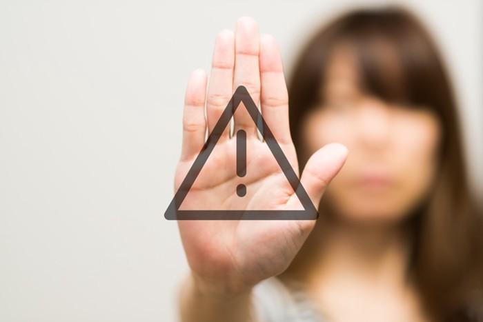 女性の手の平に「注意」のマーク
