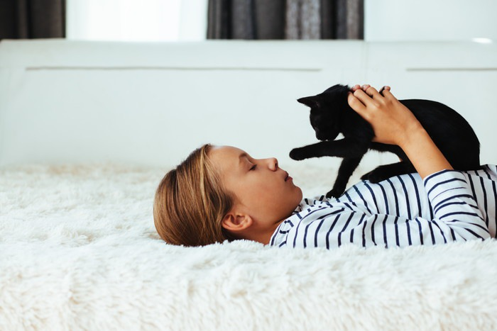 子供に抱かれる黒猫