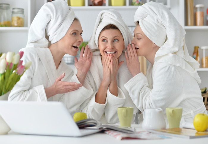内緒話をしながら楽しんでいるバスローブ姿の3人の女性