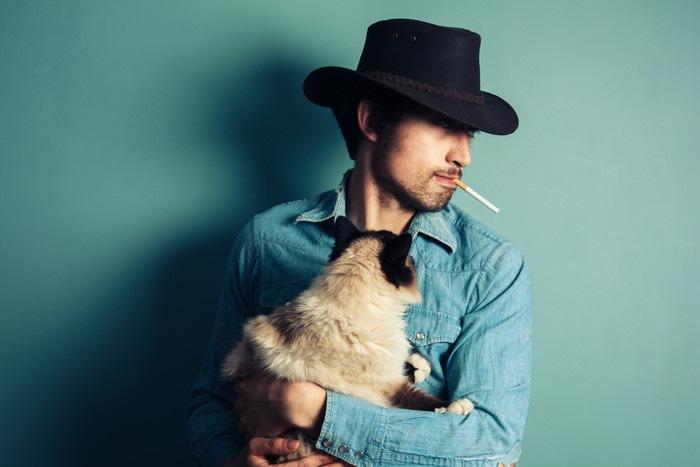 タバコを吸う男性と抱かれる猫