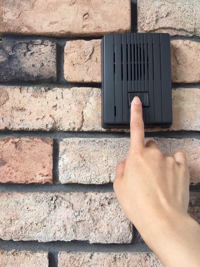 玄関のチャイムを鳴らす人の手