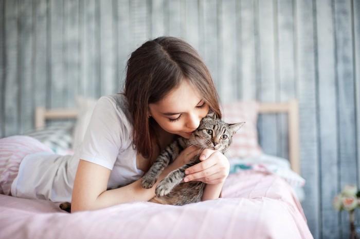 ベットで猫にキスをする女性