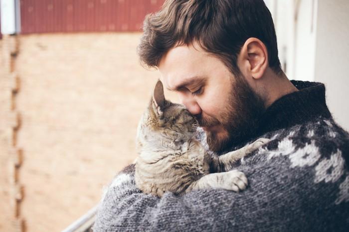 猫を抱きしめてキスをする男性