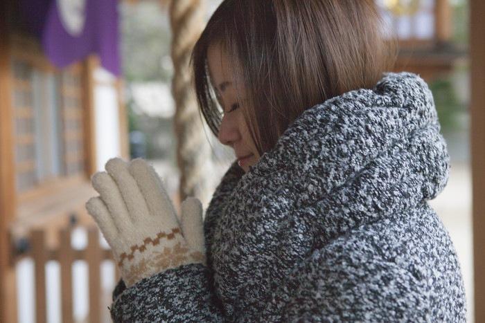 神社で祈る女性