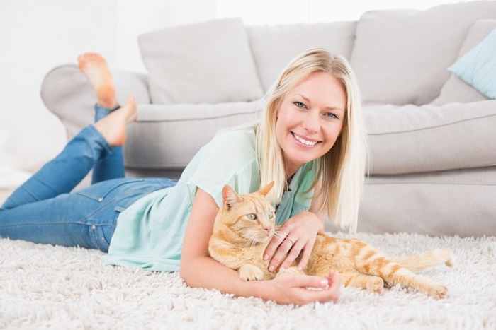 カーペットの上でくつろぐ女性と猫
