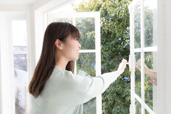 部屋の窓を閉める女性