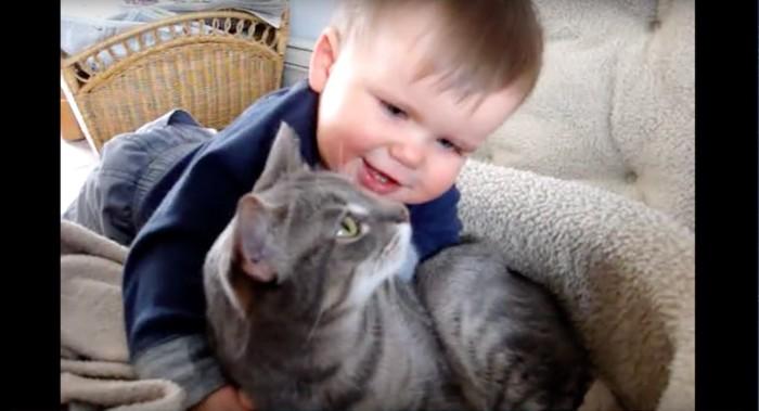 目を合わせる猫と赤ちゃん