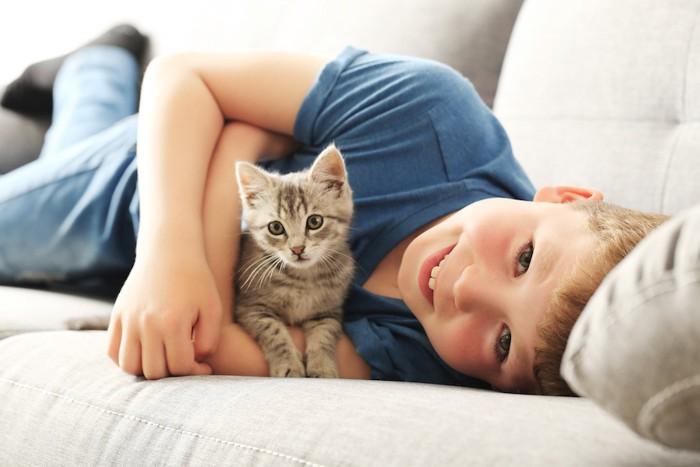 ソファーでくつろぐ少年と子猫