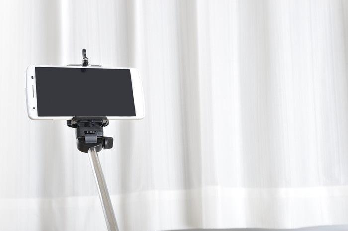 白いカーテンの前の自撮り棒とスマートフォン