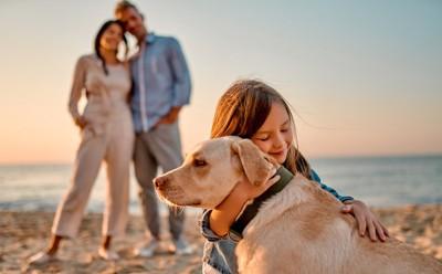 犬を抱きしめる女の子と見守る両親