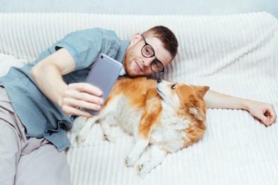 スマートフォンで犬と一緒に自撮りする男性