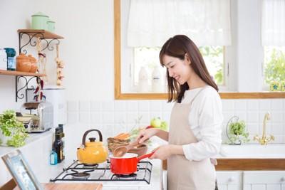 鍋を火にかける女性