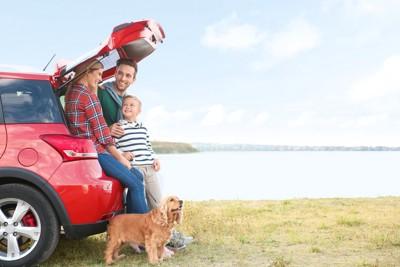 赤い車の近くに立つ家族と犬