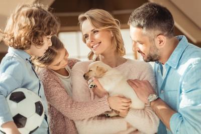 子犬を抱く女性と家族